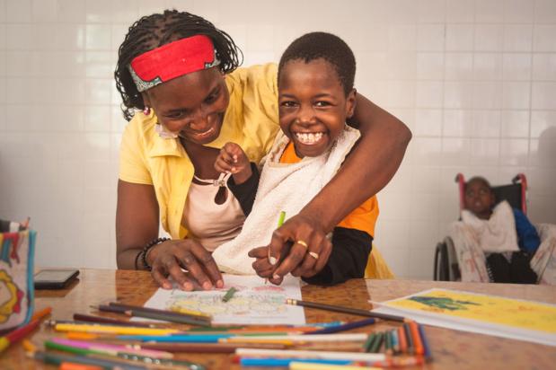 © UNICEF/Amminadab Jean Filomena, 8ans, née avec une tétraplégie spasmodique et une épilepsie, et sa mère colorient des dessins au centre de réadaptation psychosociale de Maputo, au Mozambique. (8 octobre 2018)