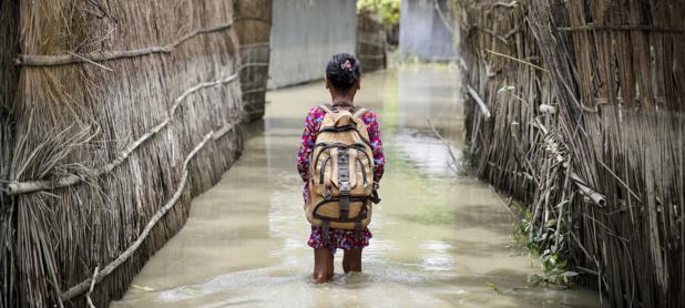 UNICEF/Akash Un enfant patauge dans les eaux en se rendant à l'école dans le district de Kurigram, dans le nord du Bangladesh, lors des inondations d'août 2016.