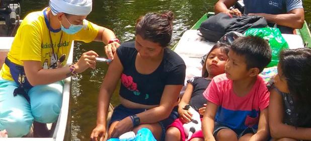 © OPS La mère d'une famille issue d'un groupe autochtone au Brésil reçoit une inoculation de Covid-19.