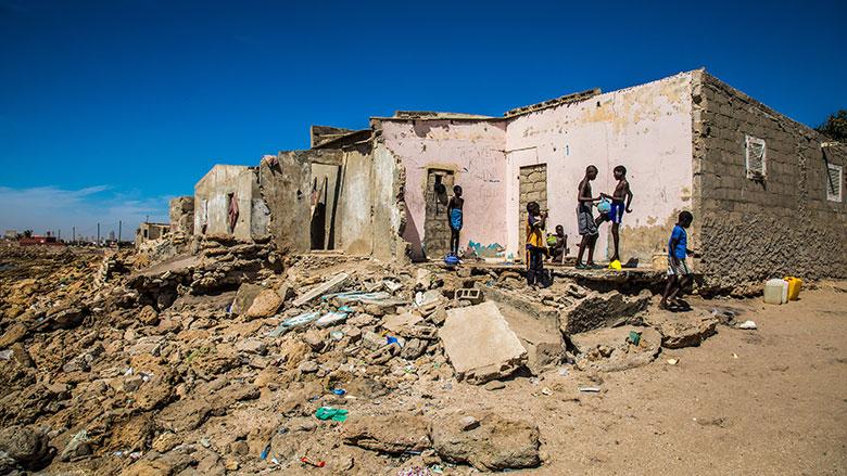 Un groupe d'adolescents se lave devant une maison détruite par la montée du niveau de la mer à Bargny au Sénégal. Photo : Vincent Tremeau/Banque mondiale