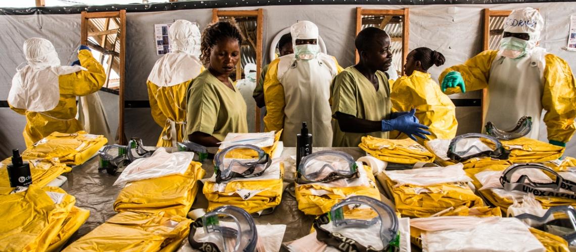 Les agents de santé mettent leur équipement de protection individuelle avant d'entrer dans la zone de quarantaine où sont traités les cas présentant un risque d'infection au virus Ebola. © Vincent Tremeau / Banque mondiale