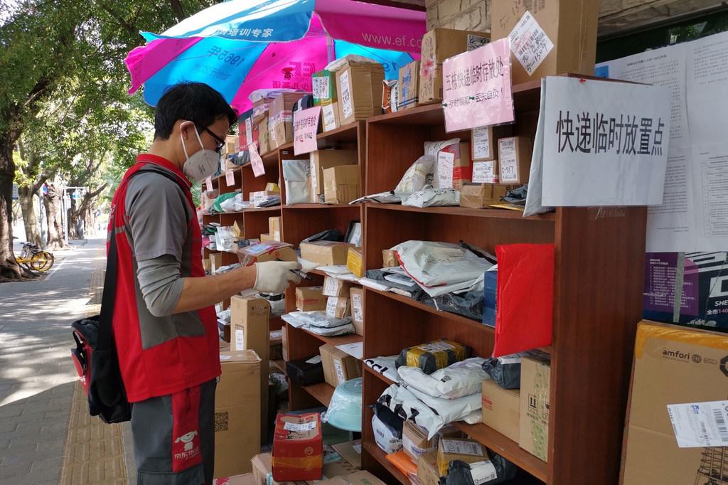 Photo Man Yi Un homme dépose un paquet à l'extérieur car il n'est pas autorisé à entrer dans les bâtiments pendant l'épidémie de coronavirus en Chine.